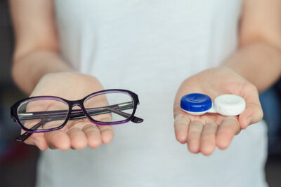 A woman is holding a pair of glasses and a contact lens case