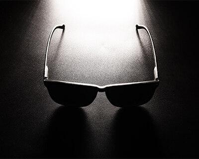 Dark sunglasses displayed in shadow