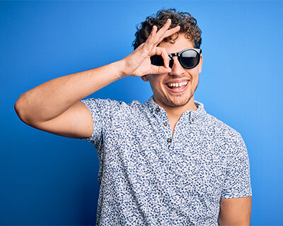 Smiling young man wearing sunglasses looks through fingers