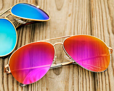 Two pairs of sunglasses with brightly-tinted lenses