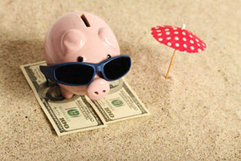 Piggy bank on the beach with sunglasses