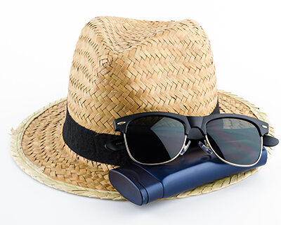 A pair of sunglasses and a straw hat displayed together