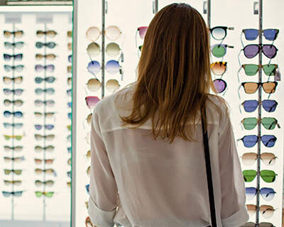 A woman looks at a wall display of sunglasses in a store