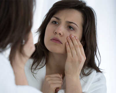A woman looks in a mirror at the dark circles under her eyes.