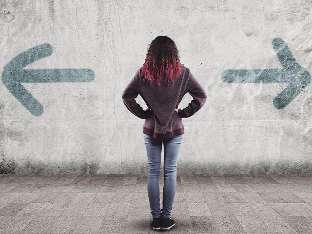 woman facing a wall with two arrows pointing in opposite directions