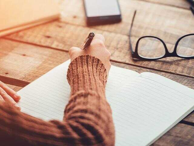 woman writing a list with pen and paper
