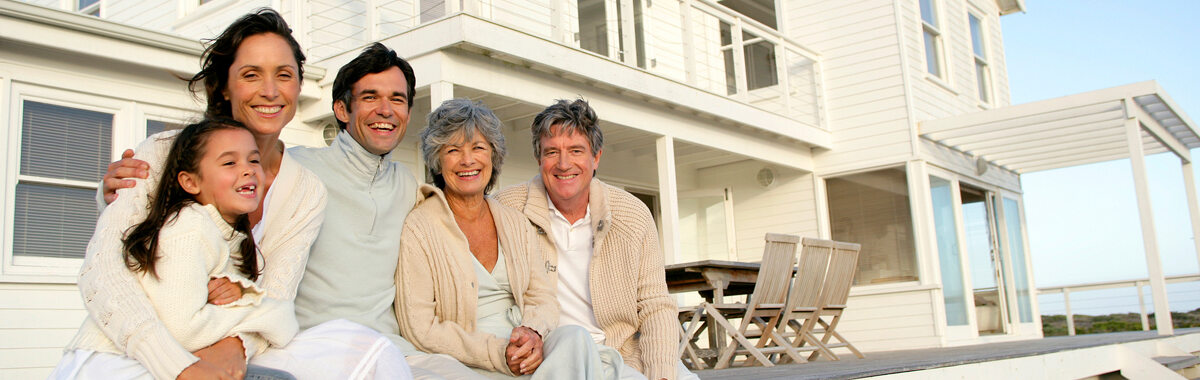 A family sitting on the front porch of a vacation rental enjoying their group trip