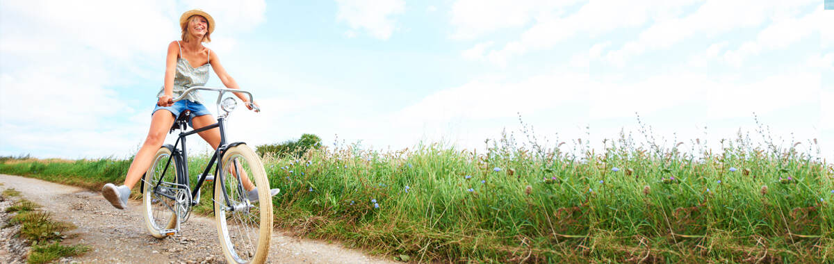 Header image of a happy woman on a bicycle traveling down a path in a field, looks like she has peace of mind