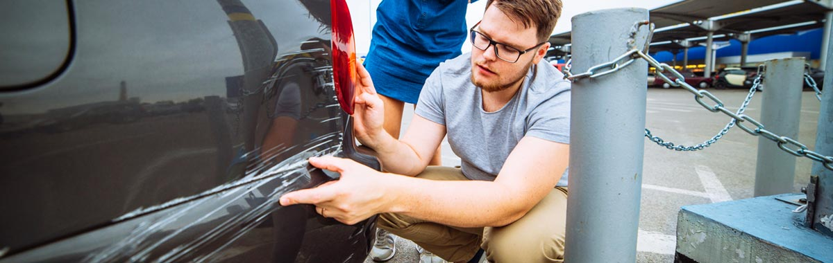 man inspecting damage to his rental car
