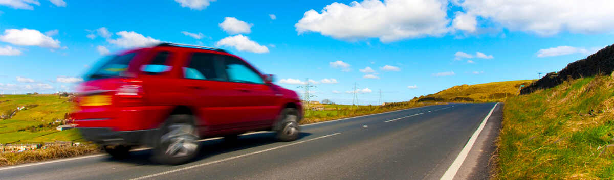 red car driving on road