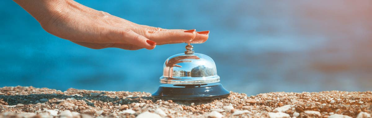 Travel concierge bell on beach