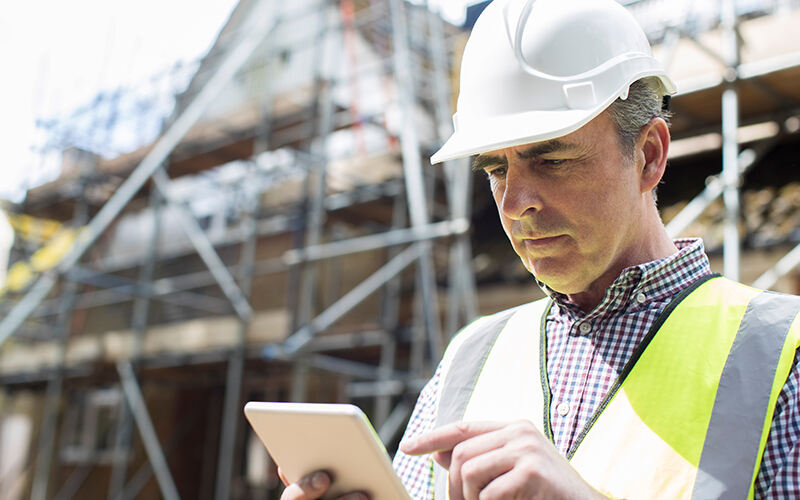 Man using BuildTools construction management software on tablet.