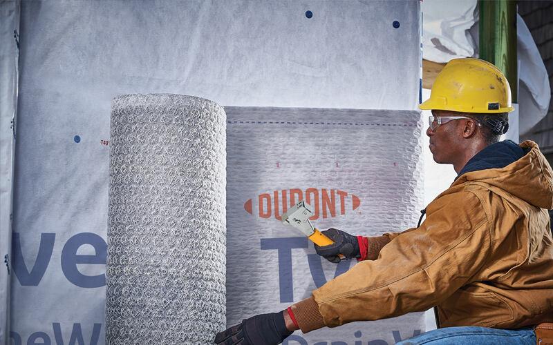 Man installs DuPont™ Tyvek® DrainVent™ Rainscreen.