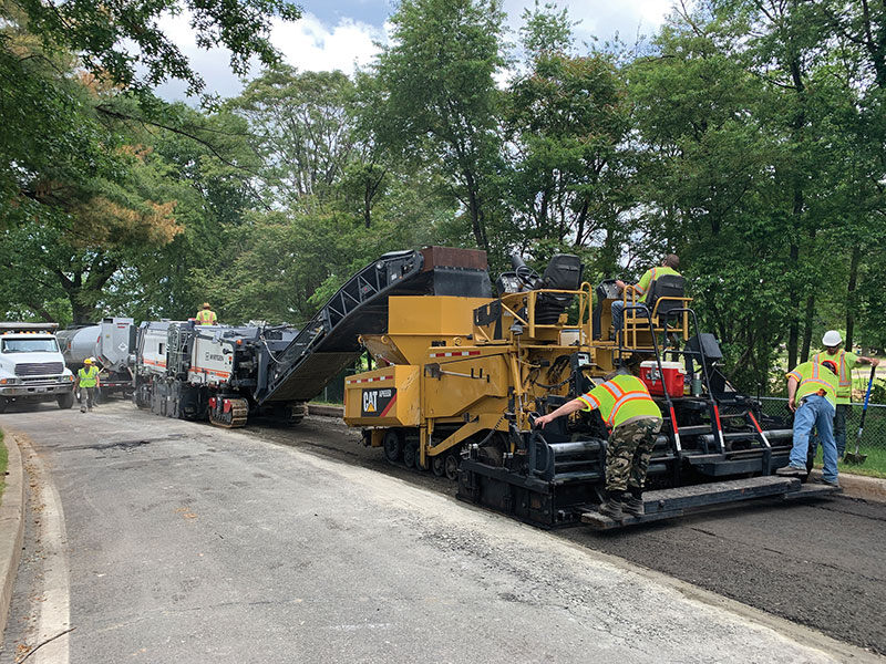 The paving train included an asphalt tanker semi-trailer pushed by a Wirtgen 3800 CR recycler, discharging into a Cat AP665D paver.