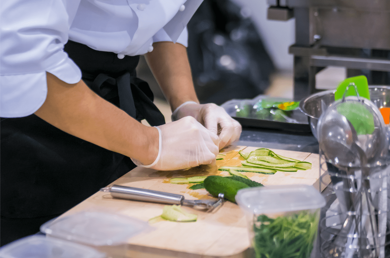 Chef wearing gloves prepping food