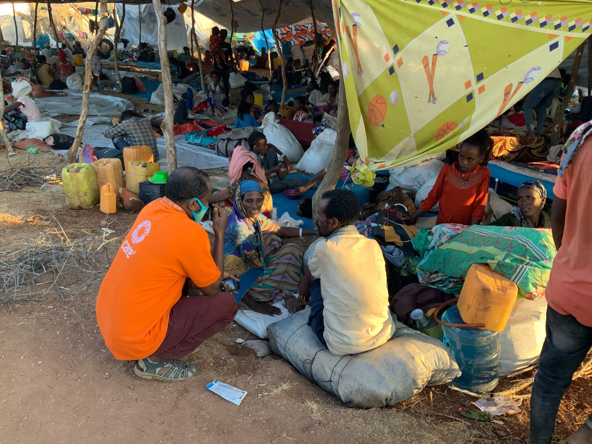 A man in a CARE shirt squats to speak with a family partially sitting under a covering of tarps and blankets.