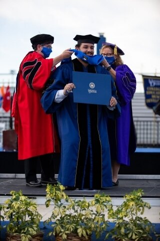 Prof. Nancy Getchell (left) and Dean Kathy Matt of the College of Health Sciences place the hood on Reza Koiler, who earned his doctorate in biomechanics and movement science.