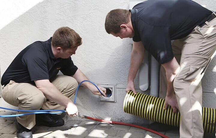 Stanley Steemer technicians inspecting a dryer vent opening on the exterior of a home.