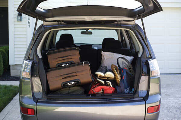 Trunk door of a mini van opened showing suitcases and travel gear