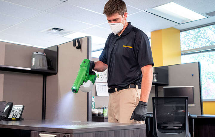 Technician disinfecting with electrostatic sprayer