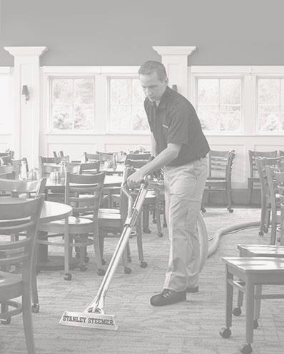 Stanley Steemer technician cleaning the carpet at a restaurant.