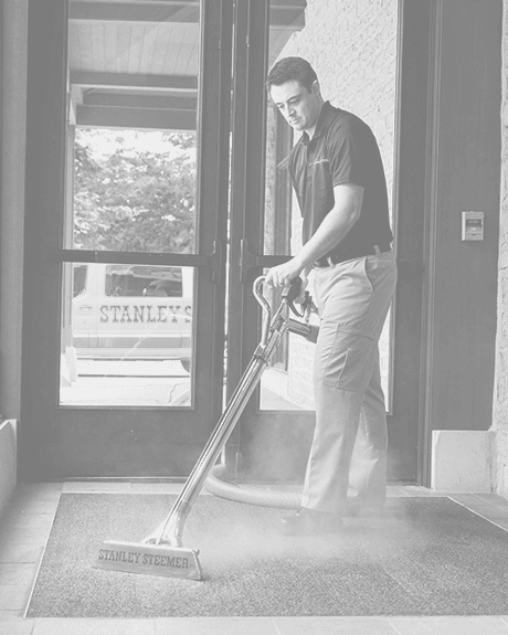 Stanley Steemer technician cleaning carpet in event space lobby