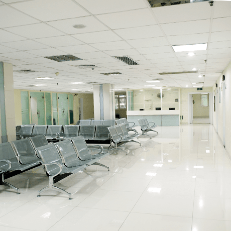 Waiting room inside hospital with white tile floors