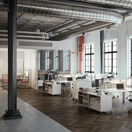 Desks inside industrial building with vents showing