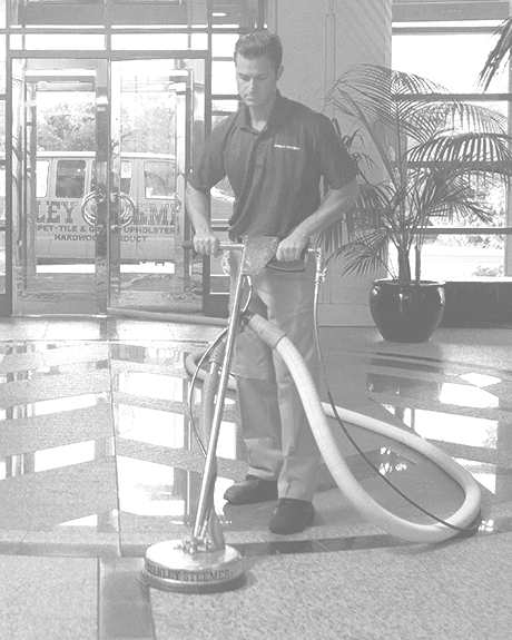 Black and white image of Stanley Steemer technician deep cleaning tile and grout floors in office lobby