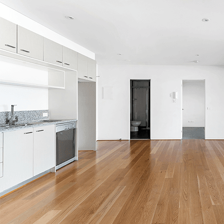Empty apartment overlooking hardwood floors in kitchen and living space