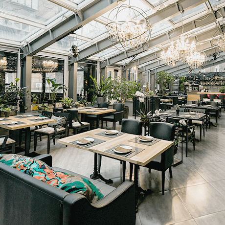 Restaurant with natural lighting, wood tables, and plants