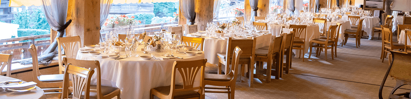 Round tables and chairs near windows in restaurant