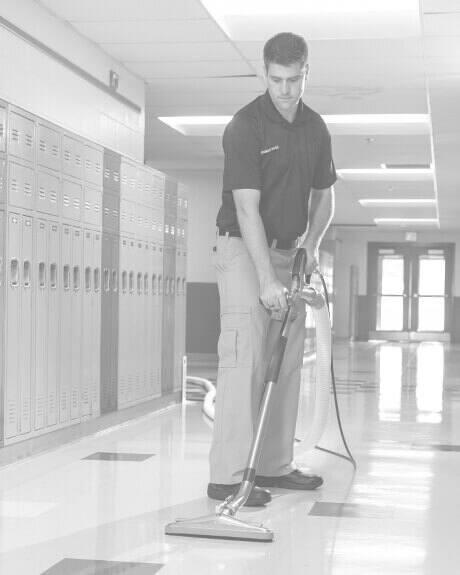 Stanley Steemer technician cleaning VCT floors in school hallway