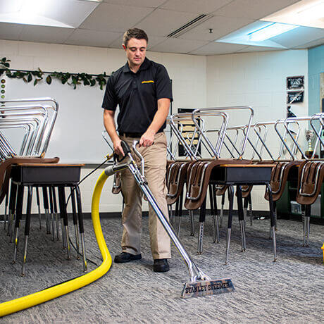Stanley Steemer technician cleaning carpet in classroom