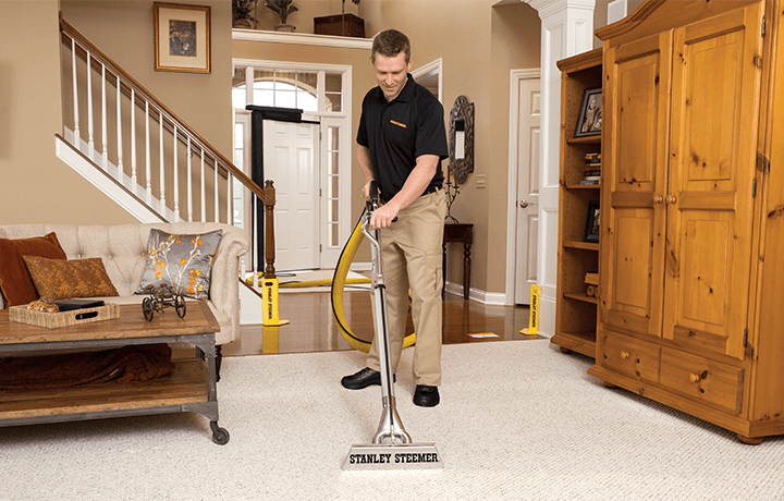 Technician using hot water extraction to clean carpets