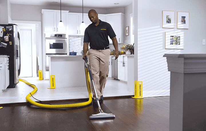 Stanley Steemer technician cleaning hardwood floors in dining room