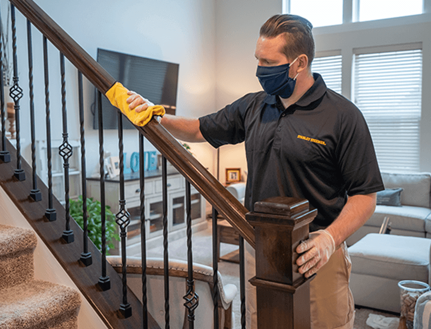 Technician disinfecting handrail