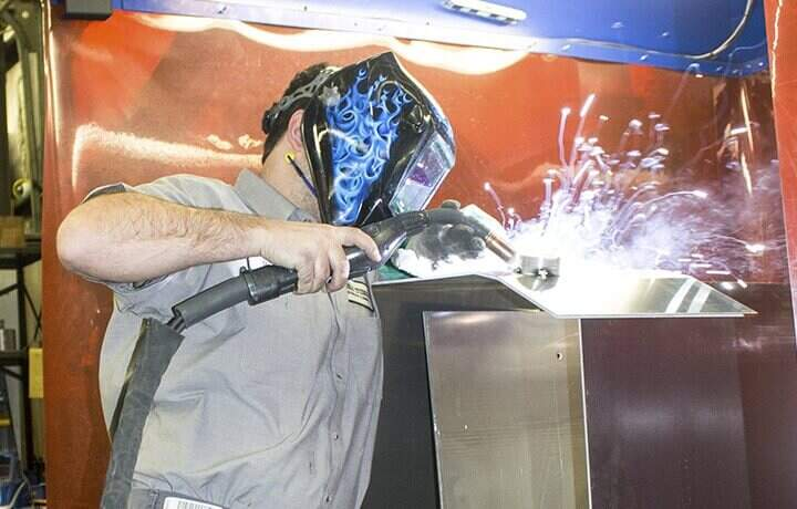 Metal smith worker with a face mask on and sparks flying.