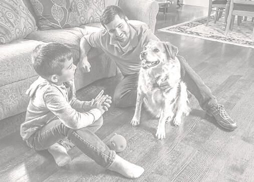 Father and son sitting on hardwood floors with their dog.