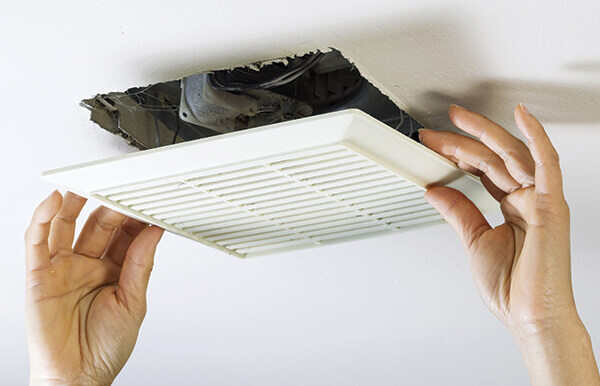 Person cleaning off air vent grate for cleaner air ducts