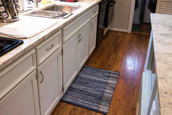 Small floor cotton rug near kitchen sink protecting the floors