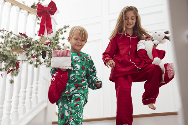 One boy and one girl walking down the stairs during Christmas