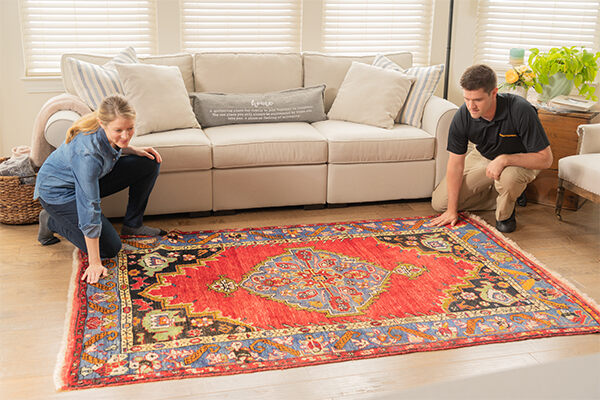 Stanley Steemer technician inspecting rug with customer
