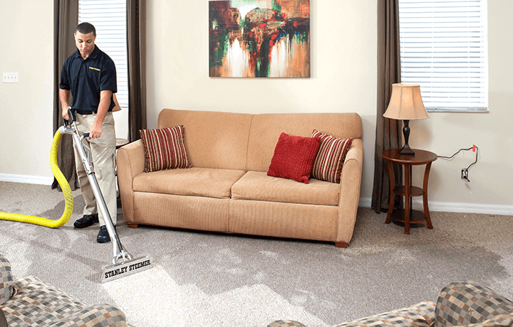 Stanley Steemer technician extracting water from carpet in living room