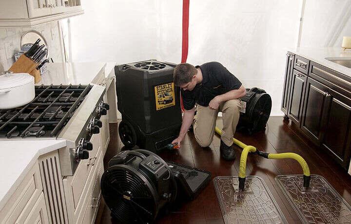 Stanley Steemer technician setting up water damage restoration equipment in kitchen.