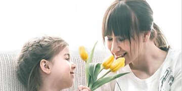 mother and daugther smelling flowers