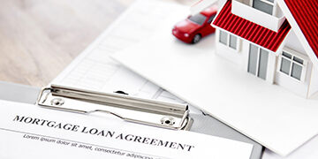 real estate mortgage loan agreement paper with house model on the table