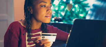 holding credit card in front of laptop