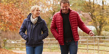 couple in their 40s walking dog