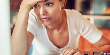 woman stressed while looking at her laptop